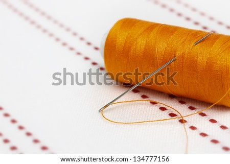 Bobbin of orange thread with needle on fabric. Sew accessories on blurred background.