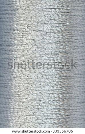 bobbin of silver thread background texture macro - stock photo