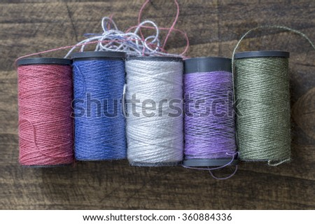 bobbins with thread on the table, from above - stock photo