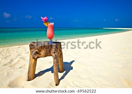 Bocal of cocktail is on original  beach table is made from trunk of tree - stock photo