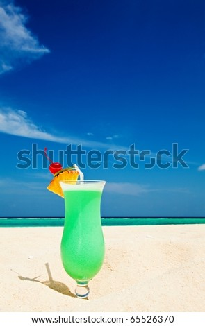 Bocal of fruity cocktail is on a sandy beach - stock photo