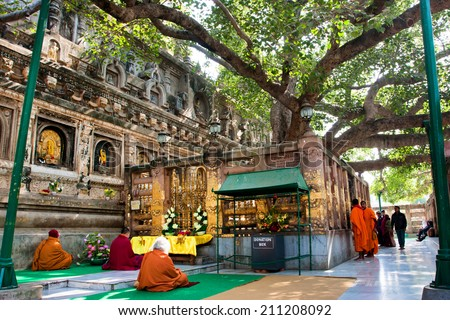 BODH GAYA, INDIA - JAN 9: Tourists and monks meditating around the holy Bodhy tree, where the Buddha attained enlightenment on January 9, 2013. It is one of the 4 holy sites related to life of Buddha - stock photo