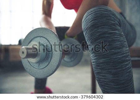 Body and mind workout in loft fitness studio. Closeup on fitness woman holding dumbbell in loft gym - stock photo