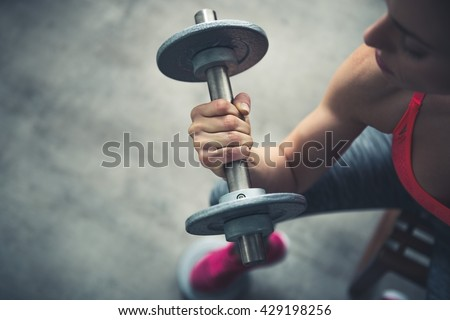 Body and mind workout in loft fitness studio. Closeup on fitness woman workout with dumbbell in urban loft gym