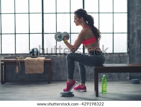 Body and mind workout in loft fitness studio. Fitness woman lifting dumbbell in urban loft gym