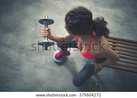 Body and mind workout in loft fitness studio. Seen from above fitness woman lifting dumbbell - stock photo