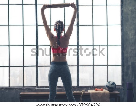 Body and mind workout in loft fitness studio. Seen from behind fitness woman with towel in loft gym - stock photo