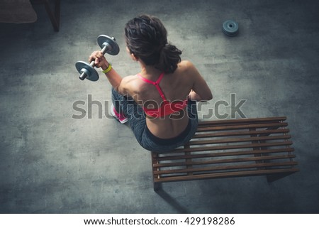 Body and mind workout in loft fitness studio. Upper view on fitness woman lifting dumbbell in urban loft gym - stock photo