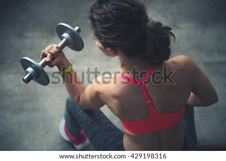 Body and mind workout in loft fitness studio. Upper view on fitness woman workout with dumbbell in urban loft gym - stock photo