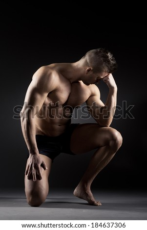 Body builder posing and showing off bicep muscle on dark background. - stock photo