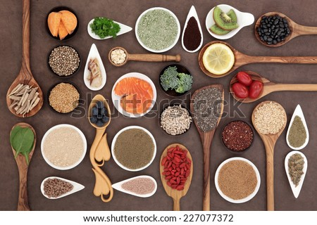 Body building and super health food selection with supplement powders in bowls and spoons over lokta paper background.  - stock photo