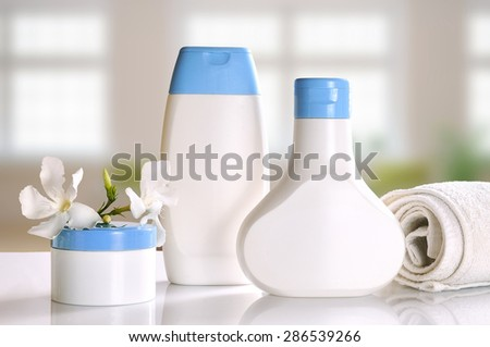 body care and beauty products on a white table glass in a bathroom front view - stock photo