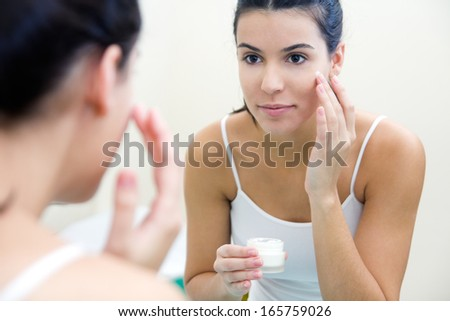 Body care. Close up portrait of Woman applying cream on face - stock photo