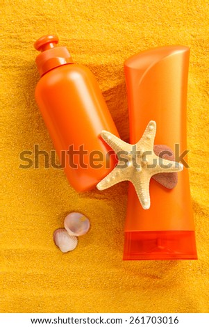 Body care  products  and shells on yellow sand. Focus on bottles and parts of starfish. - stock photo