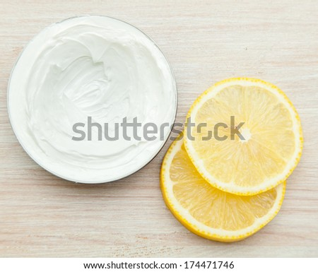body cream and lemon slices on the wooden table. top view
