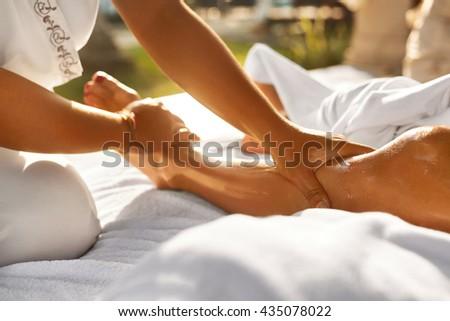 stock photo spa woman aromatherapy oil leg massage therapy masseur massaging sexy young long female