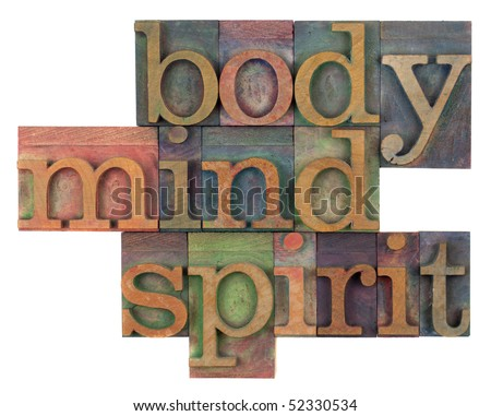 body, mind and spirit in vintage wooden letterpress types, stained by ink in different colors, isolated on white