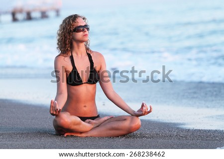 Body of a beautiful girl in a meditation on beach. Lotus position, relax concept - stock photo