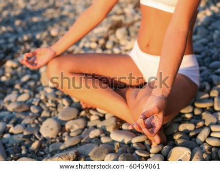 body of a beautiful girl in a meditation on the beach - stock photo