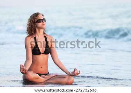 Body of a beautiful girl in a meditation on water. Lotus position, relax concept - stock photo
