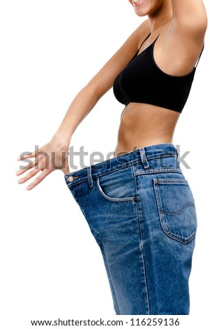 Body of a slim girl wearing huge jeans, isolated on white - stock photo
