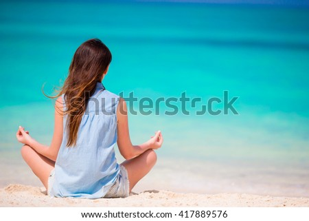 Body of beautiful woman in a meditation on the beach - stock photo