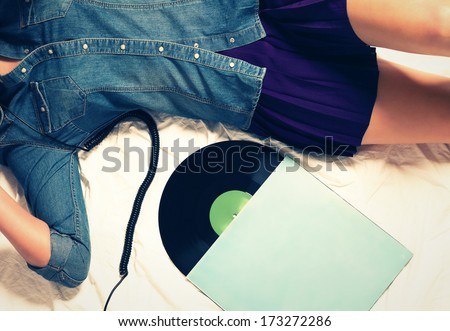 body of woman wearing jeans button down and a skirt on bed with a vinyl record