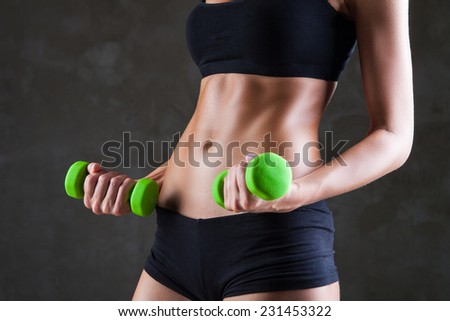 Body of young fit woman lifting dumbbells over dark grey background - stock photo