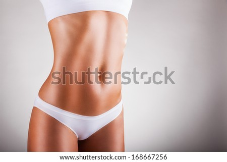 Body of young woman in white panties on a gray background - stock photo