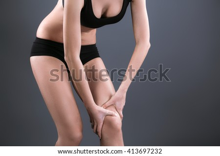 Body pain. Close up studio shot of woman. Woman suffering from knee pain - stock photo