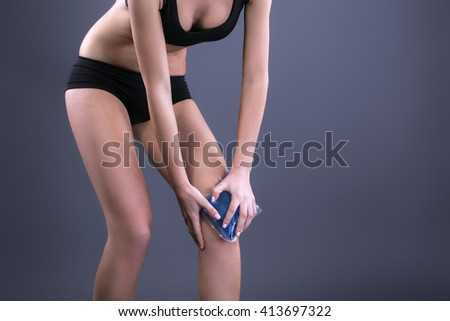 Body pain. Close up studio shot of woman. Woman suffering from knee pain. Woman holding freezing gel on knee - stock photo