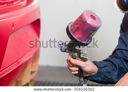 Body painter with airgun spraying red paint on a car - stock photo
