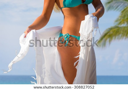 Body part of woman with perfect body on the beach, sexy slim model wearing swimwear and skirt, summer vacation concept - stock photo