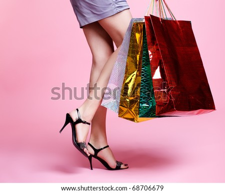 body part portrait of customer long legged girl in court shoes with shopping bags - stock photo