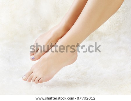 body part shot of beautiful healthy young woman's legs on white fur - stock photo