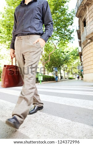 Body section low view of a businessman crossing a zebra crossing and carrying a leather briefcase in a classic city.
