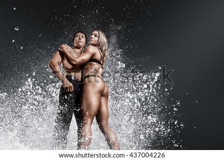 Bodybuilder athletic man and woman showing muscles with powerful powder explosion cloud - stock photo