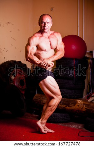Bodybuilder fexing his muscles in a gym