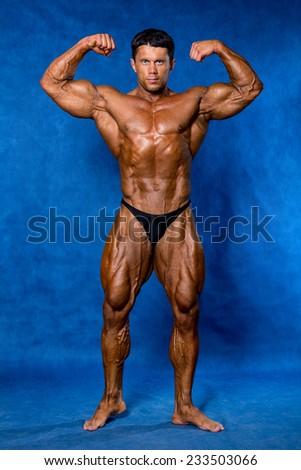 Bodybuilder flexing his muscles in studio. Mandatory poses bodybuilders. On a blue background - stock photo