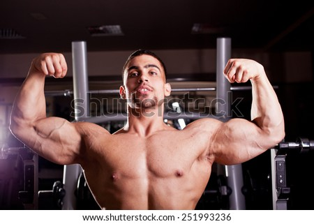 Bodybuilder flexing in a gym - stock photo