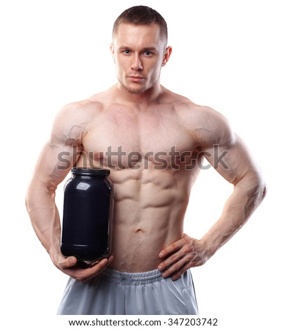 Bodybuilder holding a black plastic jar with whey protein isolated on white background. - stock photo