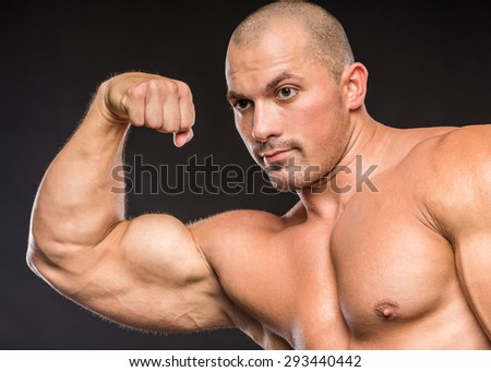 Bodybuilder in good shape against a dark background. Man posing, showing his muscle definition. - stock photo