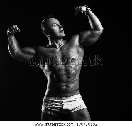 Bodybuilder in the studio on a black background