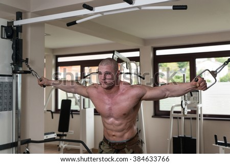 Bodybuilder Is Working On His Chest With Cable Crossover In Gym - stock photo