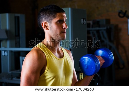Bodybuilder male shoulders deltoids vest working out in gym with dumbells - stock photo
