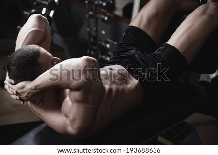 Bodybuilder man at abdominal crunch muscles exercises during training in fitness gym .Low light.  - stock photo