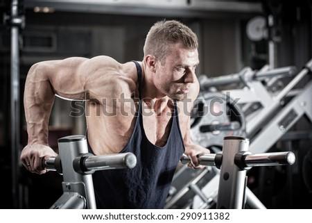 Bodybuilder man in gym doing dips as arm training  - stock photo