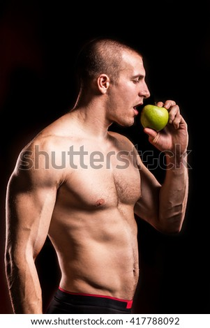 bodybuilder man with green apple isolated on black background