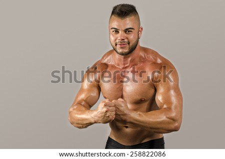 Bodybuilder man with perfect abs, shoulders,biceps, triceps and chest . Strong man flexing his muscles - stock photo