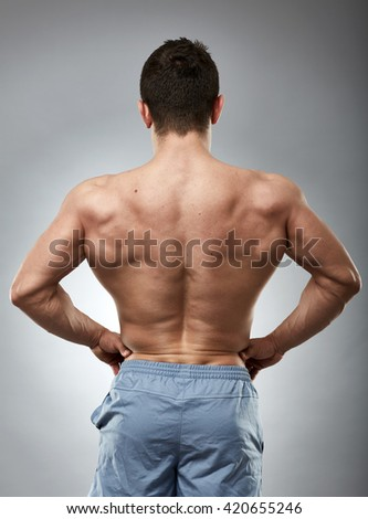Bodybuilder model showing his muscular back over gray background - stock photo